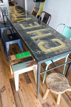 アイアンの骨に古い看板、ガラスの天板を載せたダイニングテーブル。手前のイスはオランダ人作家のもの。