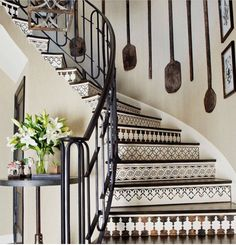 ~ A gorgeous curved Spanish-style staircase. Love the paddles placed strategically on the wall. ~