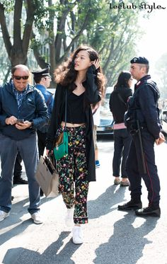 Womenswear Street Style by Ángel Robles. Fashion Photography from Milan Fashion Week. Model after the show wearing floral-print straight-leg trousers, white sneakers and black crop top. Via Bergognone, Milano.
