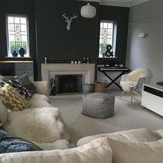 Contemporary family room.Tthe chimney breast wall is painted in Downpipe and which is softened with the other walls painted in Farrow & Ball Pavilion Gray. Faux fur throws are a great way to add to the feeling of cosiness.