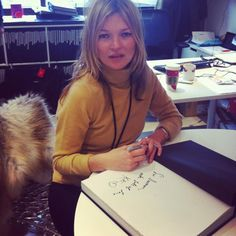 Kate autographs a copy of Kate: The Kate Moss Book during a private signing at Storm Modelling Agency.
