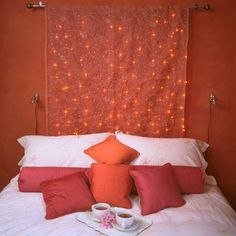 Spicy cayenne colors add hot romance to this cocoon of a space. The headboard would be easy to re-create with a swatch of fabric and fairy lights.  Source