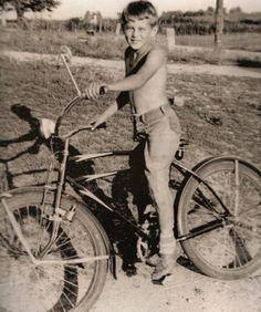 A young Jimmy / James Dean around age 9 or 10 riding his bicycle. °