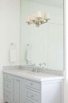 Stunning gray bathroom features a gray washstand adorned with glass knobs paired with a white quartz counter and a gray mosaic glass backsplash under a full height frameless mirror lined with a 2 light linear sconce.