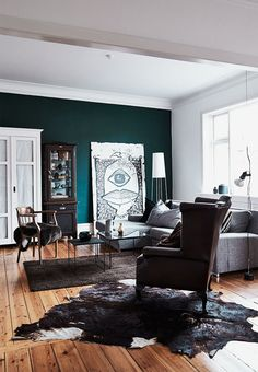 Country-feeling in this rustic, masculine and cool living room kept in braun, white, grey and black colours, with a splash of dark green on the end wall.