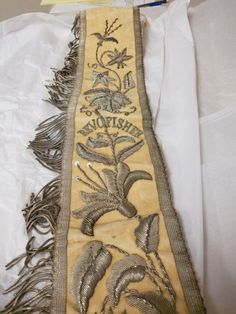 A cream velvet sash with silver metallic embroidery belonging to a Reverend Oricinth Fisher. At SU Special Collections. I am creating an oversized box in which to house this.