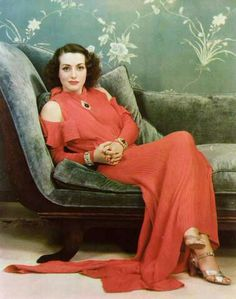 Joan in red relaxing away, wearing golden shoes.