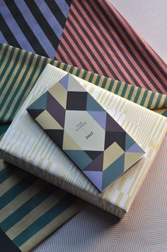 "Wrapping Paper ""The Pale Stripes"", Organic Cotton Scarf ""Aligned Black"",  Wrapping Paper ""Memphis"", Year Planner ""Mosaic"""