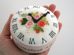 The top of this wool felt pincushion is an antique clock face with appliquéd and embroidered pink old English roses and other flowers. It is