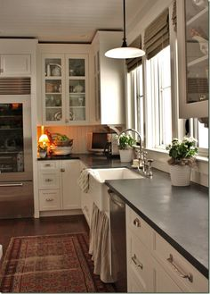 white cabinets with dark counters.  Looks like slate or concrete? I like that it isn't shiny