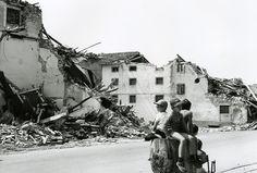 Bambini davanti a case distrutte