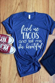"""Women's Graphic Tee - Feed me Tacos and Tell me I'm Beautiful Funny T Shirt This """"Feed me Tacos and Tell me I'm Beautiful"""" short sleeve funny graphic t shirt is sure to make any day brighter and have everyone asking you where you got this great soft shirt. Our shirts are 100% made in the USA, and we use a high-quality unisex t-shirt that is insanely soft. In fact, it will be one of the softest, best fitting, most comfortable shirts you've ever owned."""