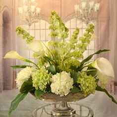 """White Calla Lilly and Bells of Ireland Silk Floral Centerpiece in Silver Bowl AR349 - Clean, crisp white silk calla lilies, Bells of Ireland, white and green silk hydrangeas arranged in a hammered, silver-toned metal pedestal vase. Our silk design provides an elegant centerpiece for dining room or coffee table decor. May be customized in various sizes to fit your needs. Measures 24"""" H x 24"""" W x 14 """" D"""