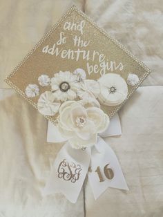Graduation cap decorated with white faux flowers, pearls, and gold glitter scrapbook paper. Ribbon is decorated with a gold glitter monogram and the year of graduation.