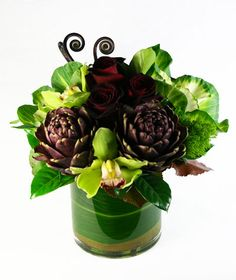on the night before our wedding, my husband made my bouquet using green cymbidium orchids, green giant calla lilies, black/burgundy mini calla lilies, fiddleheads, and the pitchers from his beloved pitcher plant wrapped in chocolate silk ribbon.  Unfortunately i do not have a photo of the bouquet, but this picture reminds me of it  :)