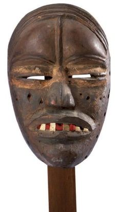 Dan. (Ivory Coast) Old mask on the forehead marked with a long vertical scarification, overlooking the slit eyes accented with a band of white pigments. The cheeks are scarified, and the wide open mouth reveals metal teeth now patina red textile use. (See reproduction) Wood. h.: 28 cm