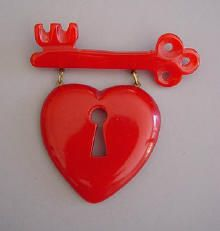 """BAKELITE green pierced and carved heart lock and key dangle bar pin, 3 1/4"""" by 3-1/4"""". in Burkholz' """"The Bakelite Jewelry Collection"""" on page 73."""