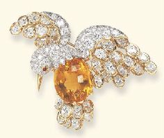 A CITRINE AND DIAMOND BROOCH, BY OSCAR HEYMAN & BROTHERS Designed as a pavé-set diamond and oval-cut citrine bird in flight, with a polished gold beak and a cabochon ruby eye, extending pavé-set diamond and oval-cut diamond openwork wings and tail, enhanced by polished gold trim, mounted in platinum and gold With jeweler's mark for Oscar Heyman & Brothers, no. 1301713
