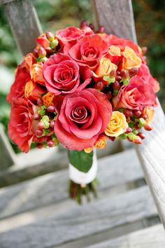 Wedding bouquet t composed of roses, spray roses, and hypericum berries
