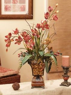 Lovely and vibrant cinnamon colored orchids stand tall in our resin footed vase, with a surrounding of natural grasses, beautifying button fern and pitcher plant there by its side. This would make a striking accent to any home or office.
