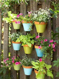balkon blumentopf an dem zaun ordnen ideen bunt blau grün dekoidee gestaltung farben rosa blumen