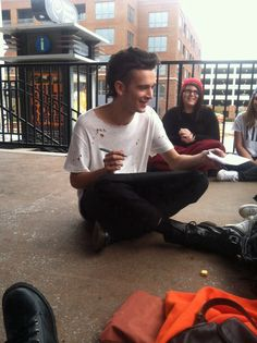 awww, look at him! just chillin with his fans on the pavement signing autographs in his worn out shirt.