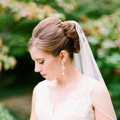 Sophisticated Updo Wedding Hairstyle. Can you get more classic than this sophisticated updo? The bride's stunning tulle veil is secured with a pretty pin.  Browse more wedding updos.