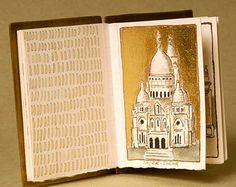 """Paris Illuminated by Laura Davidson. 2006  3"""" high  This is a miniature book filled with images of Paris painted with ink and wash with gold leaf added  The covers are brass with copper and silver elements, with a clay stone attached  It is bound with sterling silver necklace chain  Private collection"""