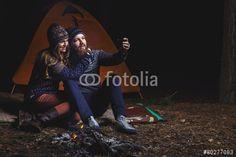 """Laden Sie das lizenzfreie Foto """"Couple tent camping in the wilderness taking selfie"""" von mikhail_kayl zum günstigen Preis auf Fotolia.com herunter. Stöbern Sie in unserer Bilddatenbank und finden Sie schnell das perfekte Stockfoto für Ihr Marketing-Projekt!"""