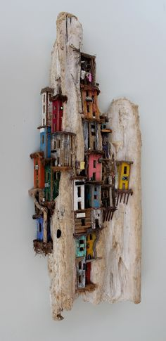 A piece of drifwood, washed ashore on Bonaire, represents the mountain like background of a small slum village.