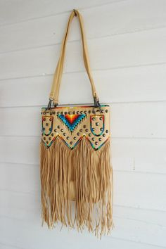 Gun metal pointed studs and fringe Dual carrying straps drop length Zippered top opening Simulated leather construction Fully lined interior includes inside zippered pocket and cell phone pouch Gun metal toned hardware Native American Fashion, Native American Jewelry, Mode Country, Western Purses, Medicine Bag, Native Beadwork, Boho Bags, Painting Leather, Estilo Boho
