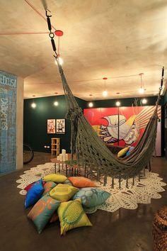 teto cinza, iluminaçao com ficaçao aparente e colorida, tapete de crochê e rede