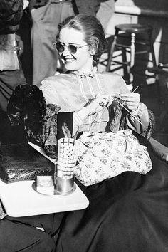 Bette Davis, wearing dark glasses while knitting on set, 1940.