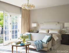 veranda, end of bed settee, mirrored coffee table, black nightstands, french doors, ivory drapes