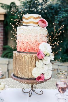 3-tiered wedding cake. Metallic gold, pink, coral and white color palette. Chevron detailing and fresh flowers.