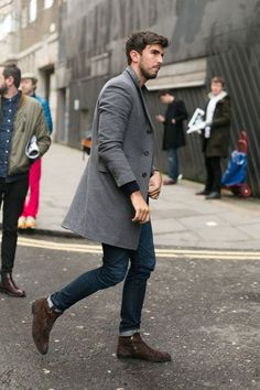 Opt for a grey overcoat and dark blue jeans if you're going for a neat, stylish look. Dark brown suede boots are a perfect choice to complete the look.  Shop this look for $248:  http://lookastic.com/men/looks/grey-overcoat-navy-jeans-dark-brown-boots-navy-crew-neck-sweater/6182  — Grey Overcoat  — Navy Jeans  — Dark Brown Suede Boots  — Navy Crew-neck Sweater