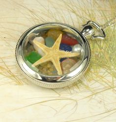 Keep the beach near your heart all day long!!This pretty stainless steel with silver-plating locket is filled with beauty of the ocean including a starfish, shells, pearl, sea pottery and some of the rarest of sea glass tinies in red, yellow, cobalt blue,  aqua and turquoise. A sprinkling of sand is thrown in for good measure. All the gems are are exquisite and were found in Northern California. Real sand fills in the gaps :)The locket has a glass front. It can open and clos...