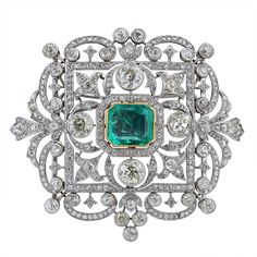 An Impressive Platinum, Emerald & Diamond Brooch/Pendant, cased by Garrard circa 1920, of fleur-de-lys cluster design, gold collet-set with a step-cut emerald of Colombian origin estimated to weigh approximately 9cts.