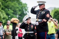 """Former United States Marine Tim Chambers gives instructions to Christian Jacobs, 6, of Hertford, N.C. as they hold salutes to honor fallen veterans as hundreds of thousands of motorcycle riders participate in Rolling Thunder's annual Memorial Day weekend """"Ride To The Wall"""", converging on the Vietnam Veterans Memorial in Washington, DC"""