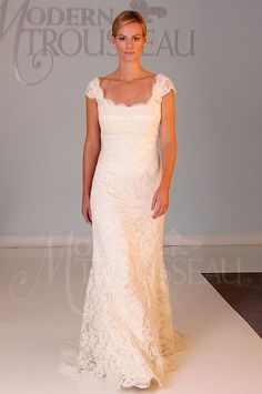 Delicate French alençon lace gown over silk charmeuse. This gown features a scoop neckline with straps. The back of the gown drapes to a deep V-shape with scalloped edges.