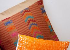 """Maggie Galton's pillows pay homage to the rebozo. Worn by Mexican women since colonial times, this distinctive accessory represents a synthesis from three cultures: the prehispanic """"mamatl"""" (cape), the Spanish """"mantilla"""" (hand embroidered silk scarf imported from the Philippines) and the macramé fringe and knotwork of the Far East."""