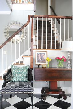 springy entryway with checkered floor, bright pillow, an simple fresh flowers