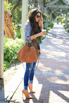 Shop this look on Lookastic:  http://lookastic.com/women/looks/button-down-shirt-and-vest-and-tote-bag-and-skinny-jeans-and-pumps/3936  — Navy and White Gingham Button Down Blouse  — Dark Brown Vest  — Brown Studded Leather Tote Bag  — Blue Ripped Skinny Jeans  — Tan Leather Pumps