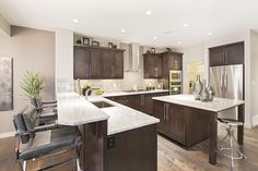 Bright marble countertops stand out against dark cabinets in the kitchen of Jayman MasterBUILTs<br></a>Allure showhome in Secord, Edmonton. Chrome fixtures and decorations complete the space<br/>and tie into the high gloss tile backsplash. Dark Cabinets, Marble Countertops, High Gloss, Backsplash, Tile, Chrome, House Ideas, Bright, Decorations