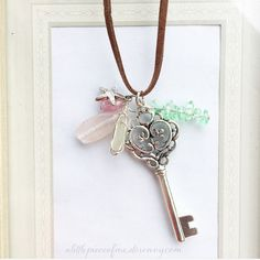 Mermaid secrets necklace with silver tone key, white wire wrapped beach glass from the beaches of Hawaii, green and pink stones, with starfish charm on brown faux suede cord. Only one available.