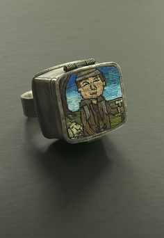 The Wanderlust ring was made in 2014 by Juan Reyes. Cynthia did a person backpacking on the cover. He is seen again on the inside with a map and a pair of binoculars.