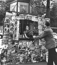Robert Doisneau - Man handing a chair to woman in a newsagent's stand on the Champs d'Elysees, 1951