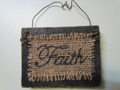 "Small, Distressed Wood Sign Painted Black With The Word ""Faith"" Neatly Written in a Cursive Font in Black on Burlap on Etsy, $9.00"