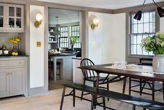 Rafe Churchill renovated Bedford NY farmhouse - modern-farmhouse-renovation-dining-room-kitchen-brass-sconces-built-in-storage Farmhouse Renovation, Farmhouse Remodel, Modern Farmhouse Kitchens, Farmhouse Table, Grey Kitchens, Dark Trim, Grey Trim, Baseboard Styles, Weekend House
