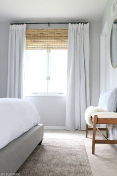 Bamboo window shades with DIY white draped curtains is a gorgeous idea for any window. Love how this makes the window look big and the space look so bright and fresh.